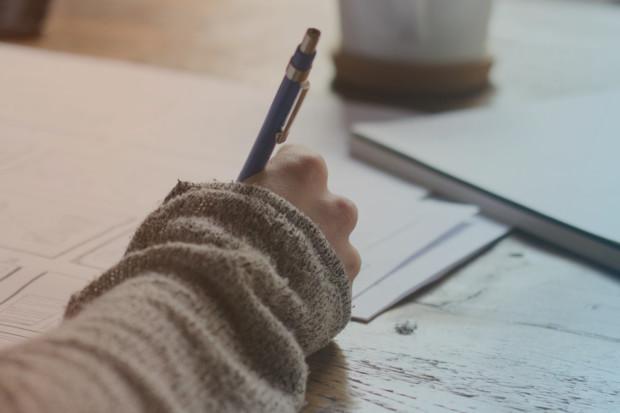 Jemand schreibt einen Text mit einem Kugelschreiber