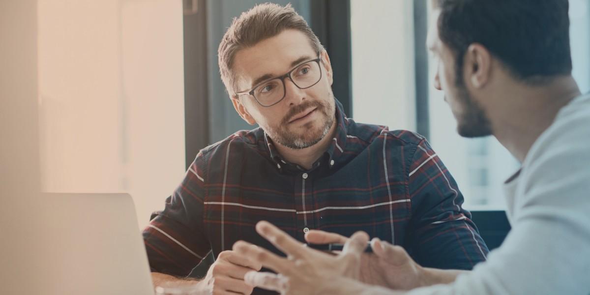 Ein Berater des Jobcenter Kreis Viersen berät einen Kunden am Laptop